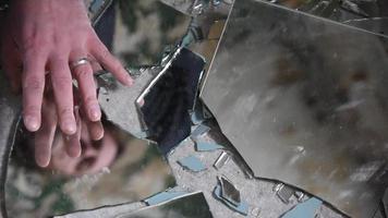 Hombre deprimido y enojado mira en fragmentos de vidrio y lo alcanza