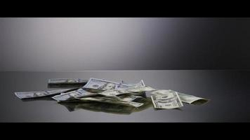 American $100 Bills Falling onto a Reflective Surface - MONEY 0032