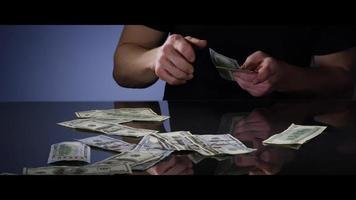 Manos de un hombre recogiendo billetes de $ 100 de una superficie reflectante - dinero 0040