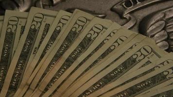 Imágenes de archivo giratorias tomadas de papel moneda estadounidense sobre un fondo de escudo de águila americana - dinero 0402 video