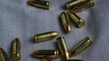 Disparo giratorio cinematográfico de balas sobre una superficie de tela - balas 087