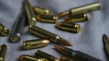 Disparo giratorio cinematográfico de balas sobre una superficie de tela - balas 095