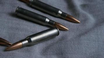 Disparo giratorio cinematográfico de balas sobre una superficie de tela - balas 107