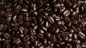 Foto giratoria de deliciosos granos de café tostados sobre una superficie blanca - granos de café 057