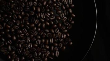 Foto giratoria de deliciosos granos de café tostados sobre una superficie blanca - granos de café 002