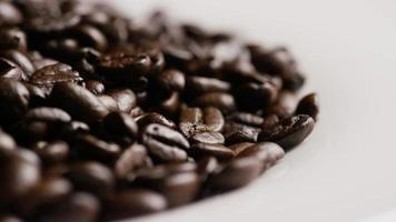 Tiro giratório de grãos de café torrados deliciosos em uma superfície branca - grãos de café 077 video