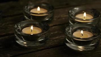 Velas de té con mechas en llamas sobre un fondo de madera - velas 005