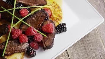 colpo rotante di un delizioso piatto di pancetta affumicata d'anatra con ananas grigliato, lamponi, more e miele - cibo 109