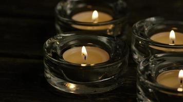 candele da tè con stoppini fiammeggianti su uno sfondo di legno - candele 020