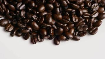 Foto giratoria de deliciosos granos de café tostados sobre una superficie blanca - granos de café 063