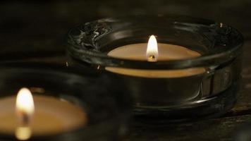 Velas de té con mechas en llamas sobre un fondo de madera - velas 010