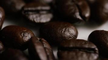 Tiro giratório de grãos de café torrados deliciosos em uma superfície branca - grãos de café 047 video