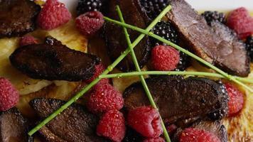 colpo rotante di un delizioso piatto di pancetta affumicata d'anatra con ananas grigliato, lamponi, more e miele - cibo 113