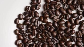 Foto giratoria de deliciosos granos de café tostados sobre una superficie blanca - granos de café 028