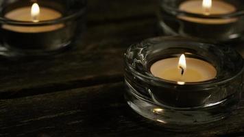 Velas de té con mechas en llamas sobre un fondo de madera - velas 007