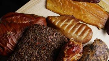Rotating shot of a variety of delicious, premium smoked meats on a wooden cutting board - FOOD 059