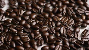 dose rotativa de deliciosos grãos de café torrados em uma superfície branca - grãos de café 040
