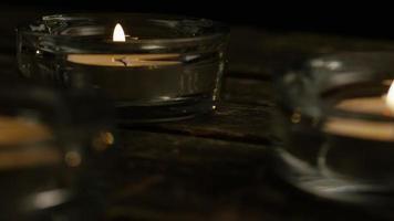 Velas de té con mechas en llamas sobre un fondo de madera - velas 012