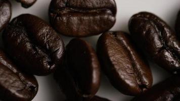 Tiro giratório de grãos de café torrados deliciosos em uma superfície branca - grãos de café 036 video