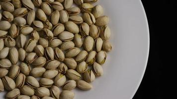 Cinematic, rotating shot of pistachios on a white surface - PISTACHIOS 002