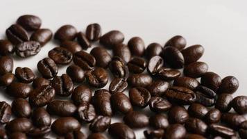 Foto giratoria de deliciosos granos de café tostados sobre una superficie blanca - granos de café 041