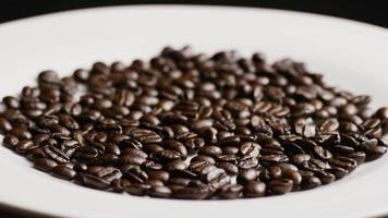 Tiro giratório de grãos de café torrados deliciosos em uma superfície branca - grãos de café 048 video
