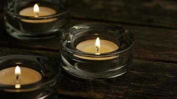 Velas de té con mechas en llamas sobre un fondo de madera - velas 008