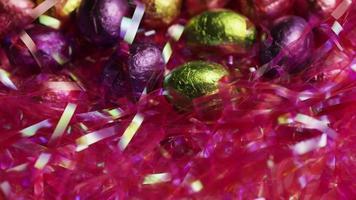 colpo rotante di caramelle colorate pasquali su un letto di erba pasquale - pasqua 209