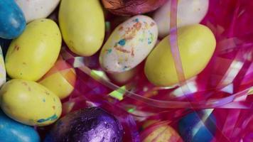 Tourné en rotation de bonbons de Pâques colorés sur un lit d'herbe de Pâques - Pâques 170