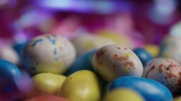 Foto giratoria de coloridos dulces de pascua sobre un lecho de pasto de pascua - pascua 155