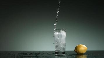 líquido transparente carbonatado que se vierte y salpica en cámara ultra lenta (1,500 fps) en un vaso lleno de hielo - líquido vertido 029