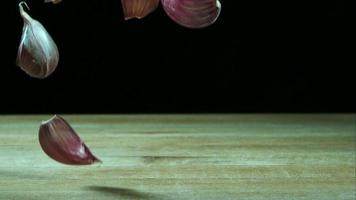 Knoblauchzehenstücke springen in Ultra-Zeitlupe (1.500 fps) auf einer Holzoberfläche - Grillphantom 033