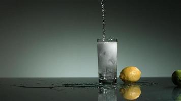 líquido transparente carbonatado vertido y salpicado en cámara ultra lenta (1,500 fps) en un vaso lleno de hielo - líquido vertido 004