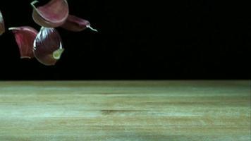 Knoblauchzehenstücke, die in Ultra-Zeitlupe (1.500 fps) auf einer Holzoberfläche hüpfen - Grillphantom 030