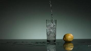 líquido transparente carbonatado que se vierte y salpica en cámara ultra lenta (1,500 fps) en un vaso lleno de hielo - líquido vertido 010