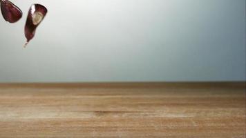Knoblauchzehenstücke springen in Ultra-Zeitlupe (1.500 fps) auf einer Holzoberfläche - Grillphantom 035