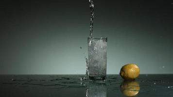 Liquide carbonaté clair versant et éclaboussant en ultra-lent mouvement (1500 images par seconde) dans un verre rempli de glace - liquide verser 011