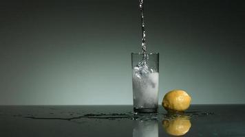 líquido transparente carbonatado que se vierte y salpica en cámara ultra lenta (1,500 fps) en un vaso lleno de hielo - líquido vertido 003