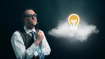 gracioso nerd o geek mirando a una nube voladora con el icono de bombilla giratoria