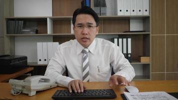 Geschäftsmannangestellter, der Tastatur tippt und Monitorcomputer betrachtet