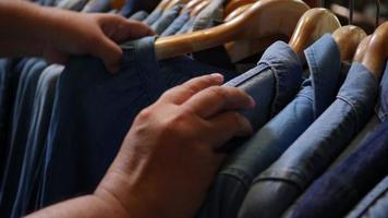 loja de roupas femininas com jeans e seleção de camisas à mão video