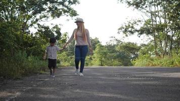 cámara lenta, madre y su hijo caminando en la calle