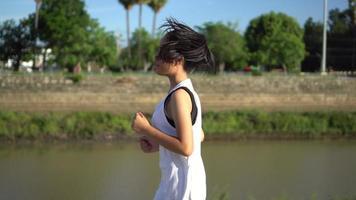 Porträt der jungen schönen asiatischen Frau, die im Park joggt