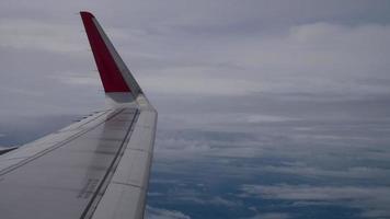 Flügel eines Flugzeugs, das über den Wolken von der Fensterebenenansicht fliegt video