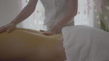 Joven recibiendo un tratamiento de exfoliación con sal en el spa aromaterapia