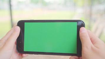 giovane donna asiatica utilizzando il dispositivo di telefono cellulare nero con schermo verde.