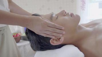 joven recibiendo masaje facial del terapeuta de spa.