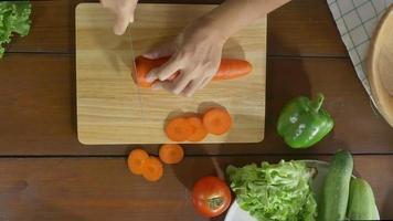 Draufsicht des Frauenchefs, der gesundes Essen des Salats macht und Karotte auf Schneidebrett in der Küche hackt.