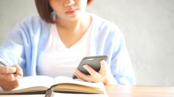 empresária usar telefone celular e escrever relatório na mesa de madeira. mulher asiática usando telefone e café. freelancer chegando na cafeteria. woking fora do estilo de vida do escritório.