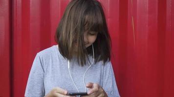 bela jovem asiática ouvindo música em um telefone inteligente na cidade. jovem mulher asiática relaxante ouvindo música na rua.